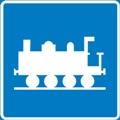 Juna. Kuvassa veturi kuvattuna sivustapäin, vasemmassa reunassa on keula, alhaalla on neljä pyörää ja kisko. Sininen tausta.