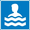 Uintipaikka. Kuvassa henkilön pää ja hartiat näkyvät vedestä, vettä kuvaa kaksi aaltoviivaa. Sininen tausta.