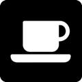 Kahvila. Kuvassa on korvallinen kahvikuppi ja asetti. Tumma tausta.