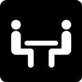 Kokoustila. Kuvassa on kaksi istuvaa henkilöä, joiden välissä on pöytätaso. Tumma tausta.