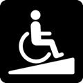 Luiska. Kuvassa on pyörätuolissa istuva henkilö menossa ylöspäin loivaa, kolmionmuotoista kaltevaa pintaa. Tumma tausta.
