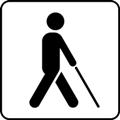 Näkövammaisia helpottavat palvelut. Kuvassa on kävelevä henkilö valkoisen kepin kanssa, kuvattuna sivusta. Valkoinen tausta.