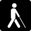 Näkövammaisia helpottavat palvelut. Kuvassa on kävelevä henkilö valkoisen kepin kanssa, kuvattuna sivusta. Tumma tausta.
