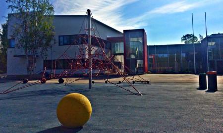 Kulosaaren ala-asteen koulu ja leikkipiha aurinkoisena päivänä.