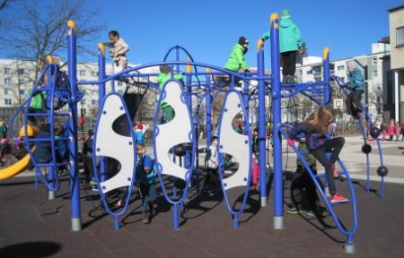 Lapsia leikkimässä kiipeilytelineellä.