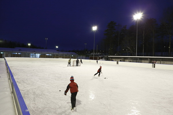 Children playing ice hockey in a artificial ice rink after dark.