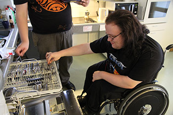 Boy in a wheelchair doing dishes.