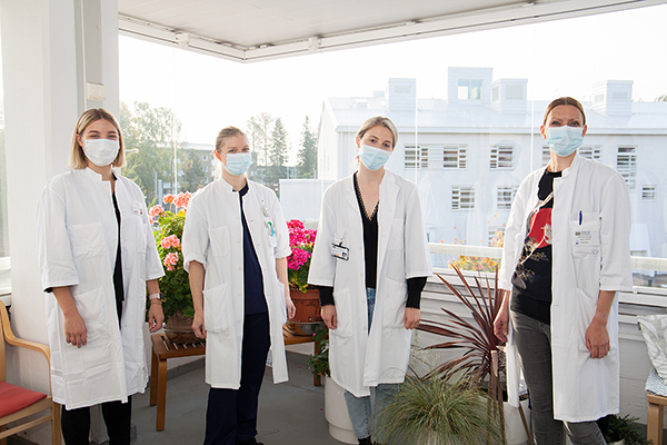 Doctors and psychologists in face masks on a balcony.