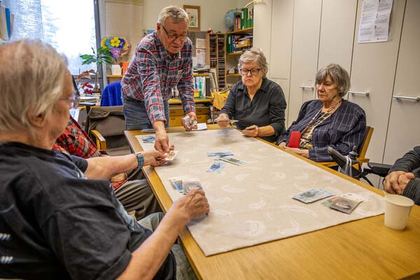 Six people sitting around a table and playing.
