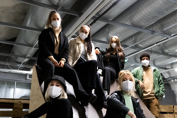 A group of young people are wearing masks.
