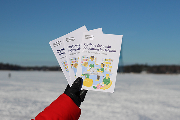 Hand holding brochues in front of a wintery scenery