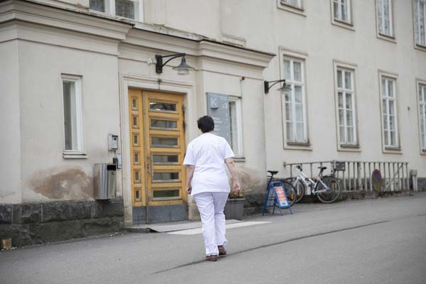 A nurse in white uniform walking towards the entrance door.