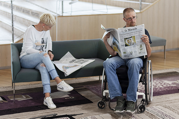 People reading newspapers at Helsinki Central Library Oodi.