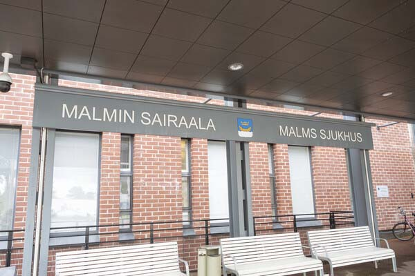 Sign of Malmi Hospital and three benches.